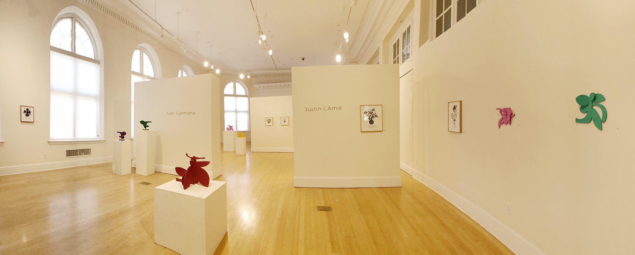 Full view of gallery with large windows and wood floors. with colorful sculptures and paintings on the walls.