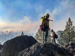 Men on tall mountain peak with smoke