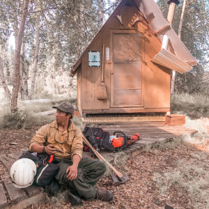 Firefighter seated on ground with pack