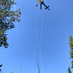 Helicopter against blue sky with ropes hanging down