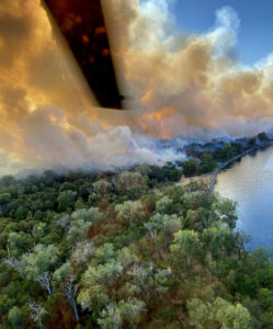 Fire in wooded area as seen from helicopter with one blade in the frame