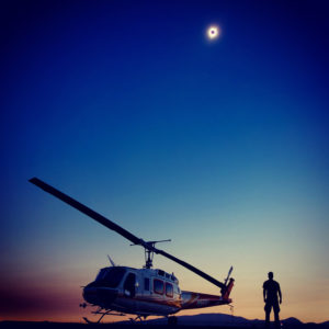 Helicopter and man silhouetted against sky at dusk with lunar eclipse above
